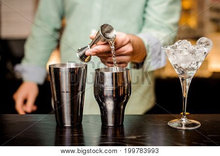 Closeup of bartender hands pouring alcoholic drink into a jigger to prepare a cocktail