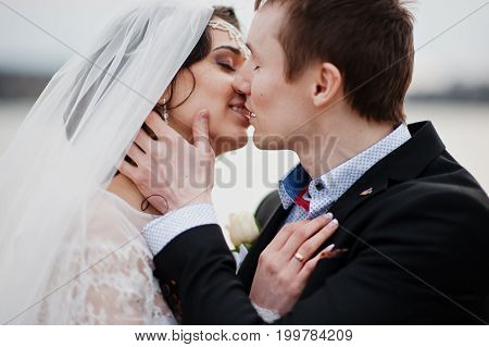 Close-up Photo Of A Kissing Wedding Couple On The Lakeside.