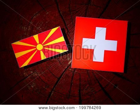 Macedonian Flag With Swiss Flag On A Tree Stump Isolated