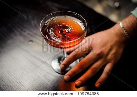 professional bartender with red cocktail into a martini glass close up