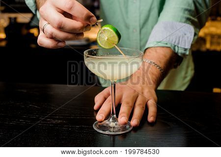 Bartender making the cocktail with lime close up