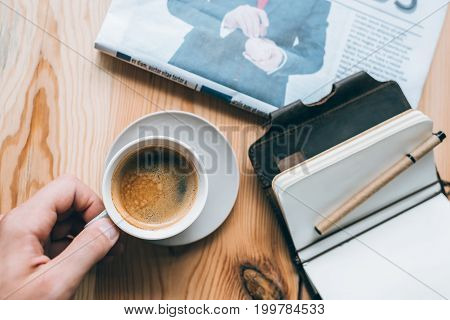 Businessman With Cup Of Coffee And Notebook On Table