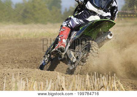 motocross racer accelerating speed in track .