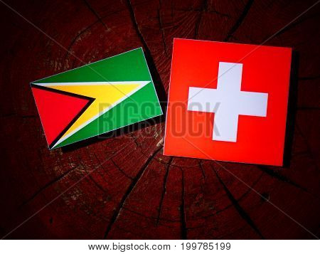 Guyana Flag With Swiss Flag On A Tree Stump Isolated