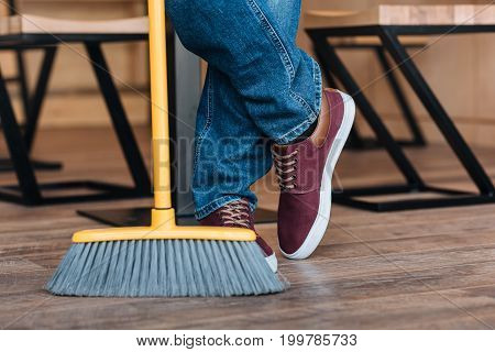partial view of worker legs and broom in coffee shop
