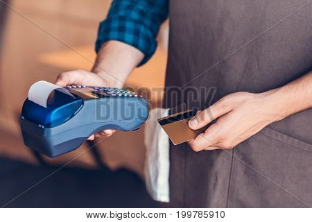 partial view of barista holding credit card and cardkey reader in hands in cafe