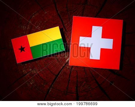 Guinea Bissau Flag With Swiss Flag On A Tree Stump Isolated