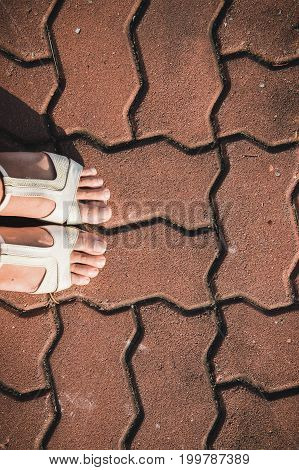 foot work woman shoe on the texture paving stone footpath background