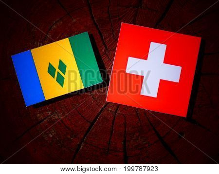 Saint Vincent And The Grenadines Flag With Swiss Flag On A Tree Stump Isolated