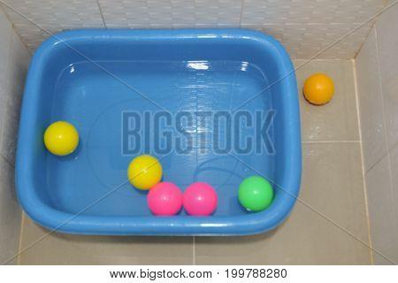 Multi colored plastic balls on plastic basin after bath baby.