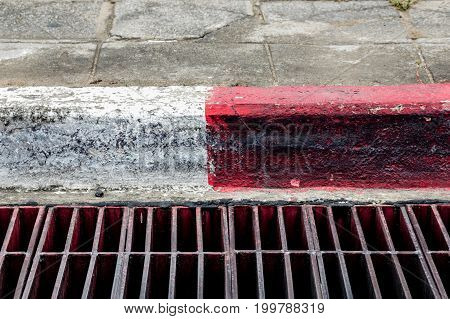 Symbol white and red color on the sidewalk for saying that is forbidden parking.