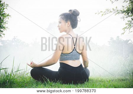 Young woman practicing yoga Everyday Yoga helps in concentration breath shape body strength help skin brighten. Among the nature in bright days