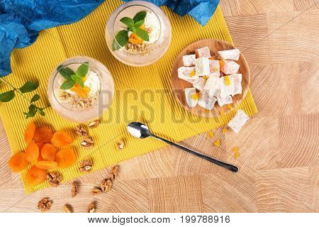 Two fruity smoothies in dessert glasses with sweets and fruits on a yellow background. Banana cocktails, Turkish Delight and dried apricots with walnuts on a colored background, top view.