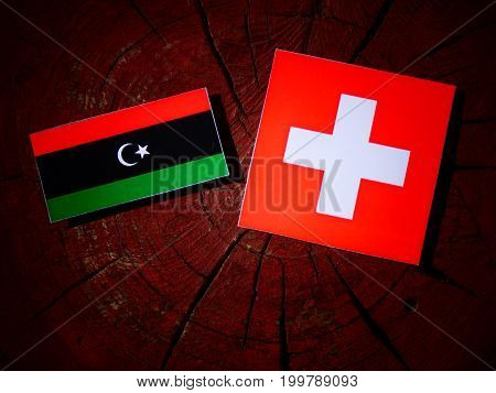 Libyan Flag With Swiss Flag On A Tree Stump Isolated