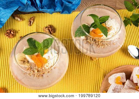 Top view of two banana smoothies in a huge glasses with Turkish Delight, dried apricots, walnuts and spoon on multi-colored background. Healthy smoothie with sweets. and fruits, close-up.
