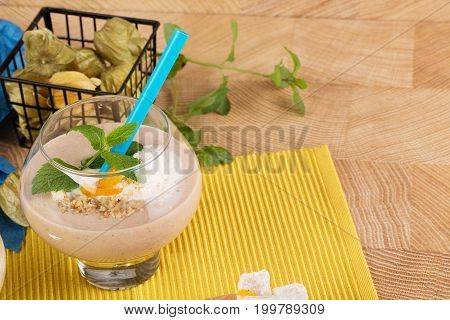 Close-up of a huge dessert glass full of fruit smoothie from ice cream, bananas, dried apricots and leaves of mint on a bright yellow background. Banana milkshake. Vegan smoothies concept.