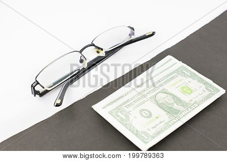 Dollars and glasses. Black and white background.