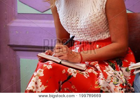 The girl writes educational material in a notebook during the training course