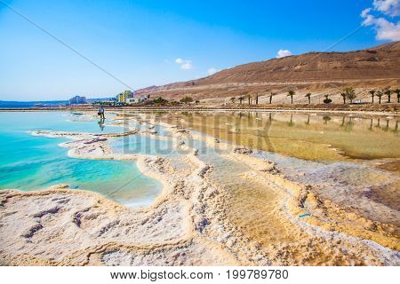 A woman is out for a walk on the Dead Sea. The concept of medical and ecological tourism. The evaporated salt has developed into fantastic patterns