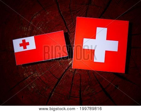 Tonga Flag With Swiss Flag On A Tree Stump Isolated