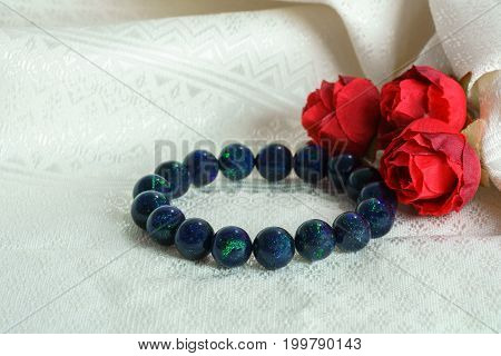 Beautiful rare Black Opal beads in bracelet with red roses on offwhite Thai silk background