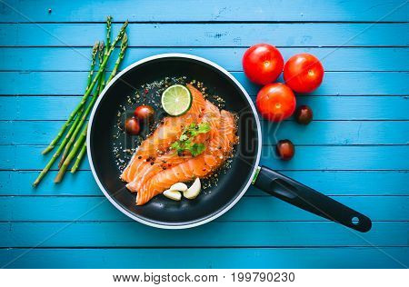 Cooking Pan With Salmon Fillets And Some Spices On A Background Of Blue Wood