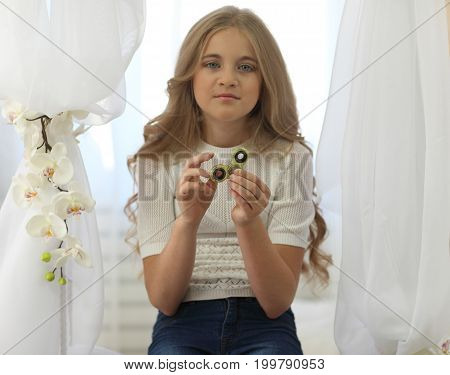 Cute Young Girl In White Shirt With Long Fair Hair Playing With Green Fidget Spinner In Bright Room