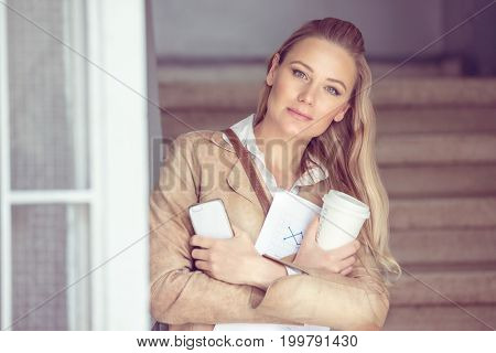 Portrait of a beautiful blond student girl with a coffee and phone, smart intelligent youth, white collar worker, back to school concept