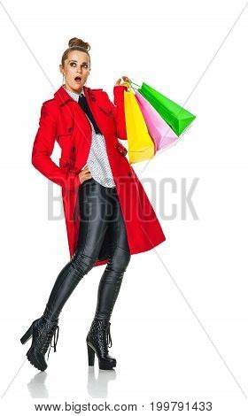 Keep the autumn bright. Full length portrait of surprised trendy woman in red coat isolated on white background with shopping bags looking on copy space