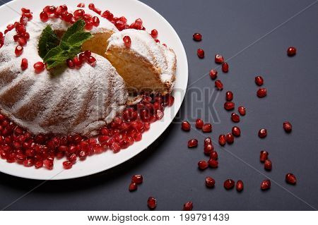 A colorful composition of plate with fresh, powdered cake and shiny garnet seeds on a purple table background. A portion of marble cake with spicy mint and berries. Traditional confectionery cuisine.