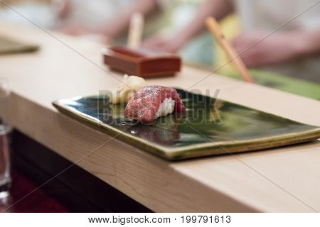 Medium fat tuna nigiri sushi with white rice on green plate with blurred chefs hands at background
