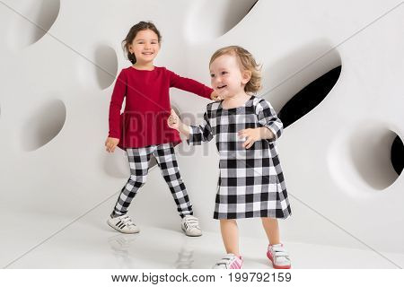 Two stylish little girls run after each other on white wall background. Children's clothing in a cage