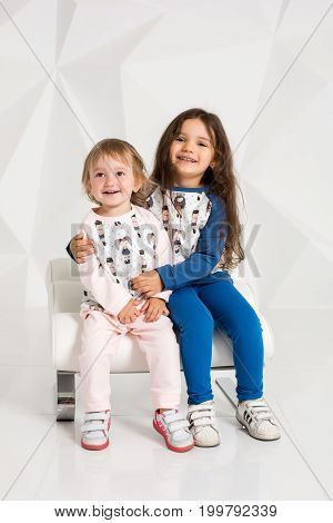 Two stylish little girls sit on one round chair on white wall background. Children's clothing