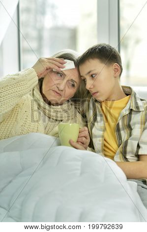 little boy taking care of his grandmother in hospital