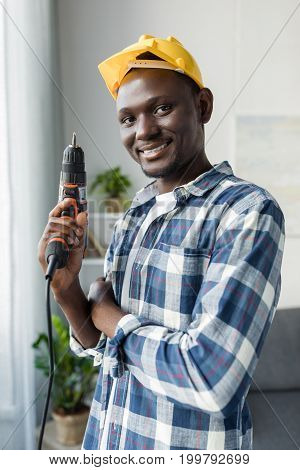 Handsome African-american Man With Perforator And Yellow Hardhat