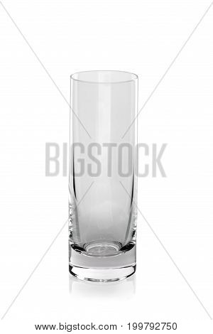 Close-up of a tall transparent glass for clear, mineral water or vodka or alcoholic beverages isolated over the white background. A modern, simple, elegant glass. Thirst and drinking concept.