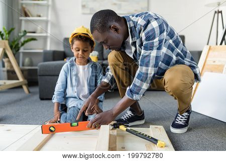 African-american Father Teaching His Little Son How To Use Tools