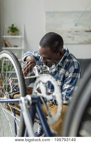 Handsome Afro Man Repairing Bicycle With Screwdriver In Living Room