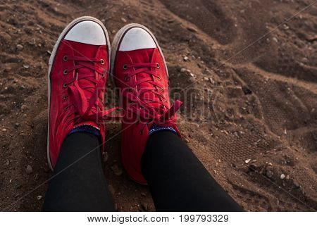 Woman legs in red shoes on the sand, relaxing on the beach