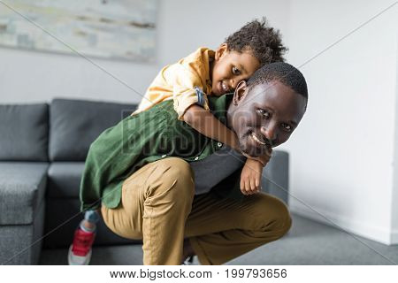 Cute Little Afro Son Piggybacking On Father At Home