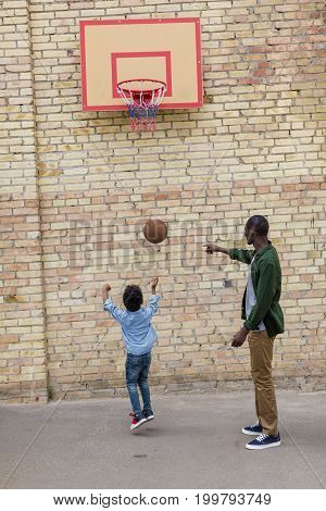 Adorable African-american Father And Son Playing Basketball Together