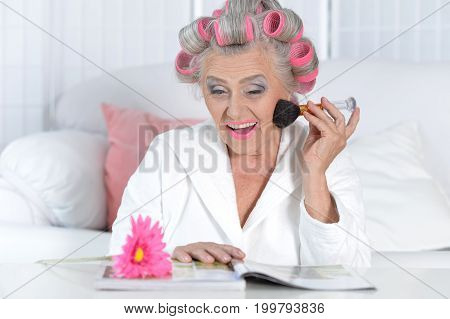 Senior woman with pink hair curlers reading magazine