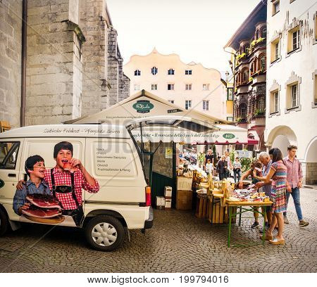 Bressanone Italy Aug 10 2017: people near a speck market stands in Trentino Alto Adige. Speck is a PGI traditional smoked ham of south tyrol