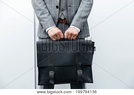 Close up of a man in suit holding briefcase isolated over white background