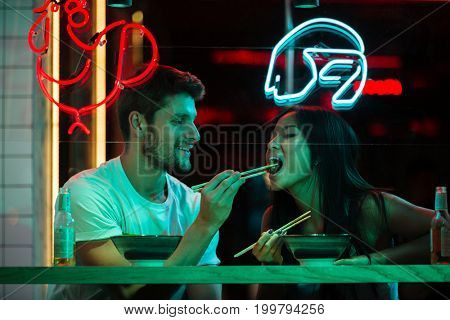Image of young multiethnic happy loving couple sitting in cafe looking aside eating.