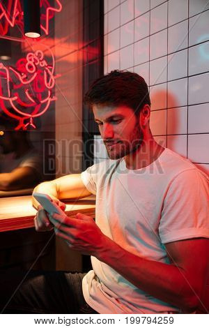 Picture of caucasian young attractive serious man sitting in cafe looking aside chatting by phone.