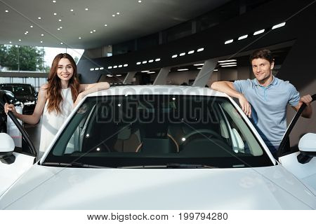 Happy young couple standing near their newly bought vehicle in a dealership