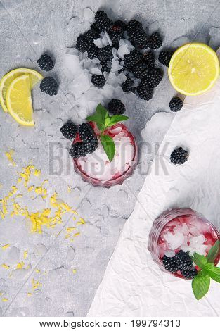 Top view of a composition of two glasses of icy beverages with peppermint and blackberries on a frozen white background. Ripe, fresh blackberries and a cut yellow lemon for a non-alcoholic smoothie.