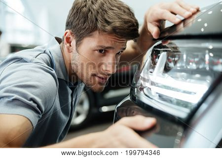 Young male customer examining and looking carefully at a new car at a dealership