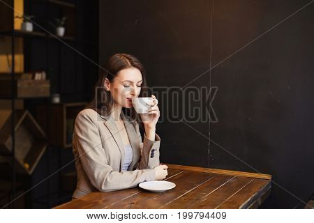 Portrait Of Young Girl Drinking Tea And Looking Out Of The Coffee Shop Window